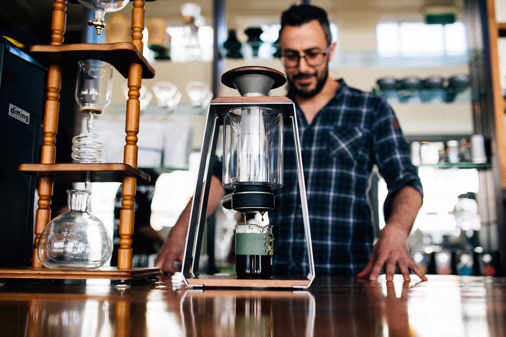 Jason Moore makes a specialty coffee using a Trinity Press	at Vanguard.