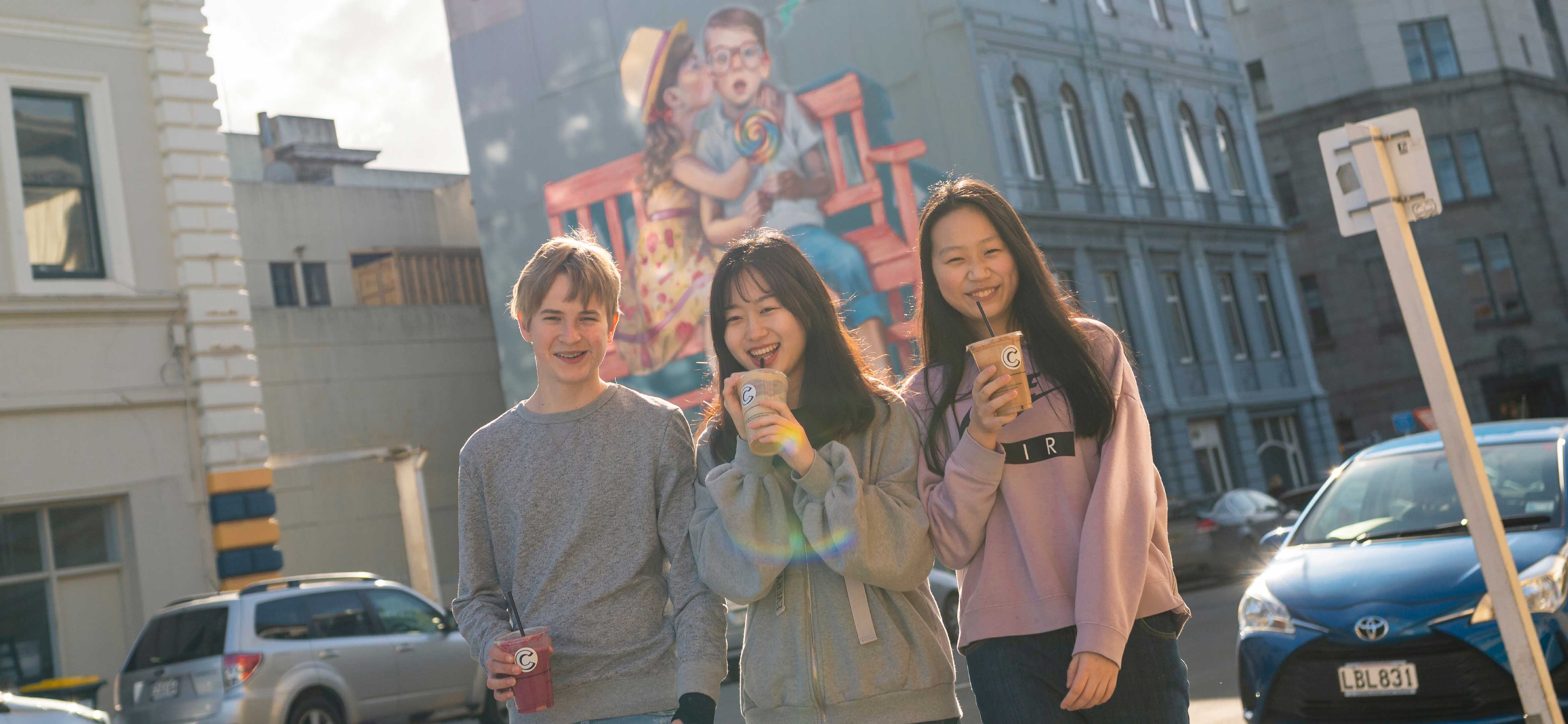 Dunedin students enjoying a drink in front of street art